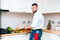 Handsome man cooking and preparing lunch. Young cook smiling and making a salad Royalty Free Stock Image