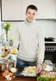 Handsome man cooking raw fish with lemon Royalty Free Stock Photo