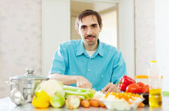Handsome  man cooking  vegetables Stock Photography