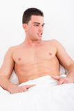 Handsome man covered in white sheets with naked torso. Lying in bed stock photos