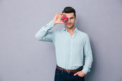 Handsome man covering his eye with gift box Stock Photo
