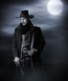 Handsome man in cowboy costume. Stay in steppe at night with full moon. Vampire Hunter Royalty Free Stock Images