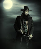 Handsome man in cowboy costume. Stay in steppe at night with full moon. Vampire Hunter Royalty Free Stock Photos