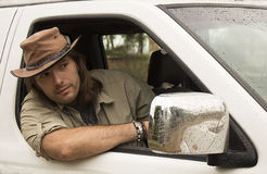 Handsome man in cowboy hat in car 4x4. Safari style. Royalty Free Stock Photography