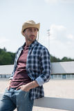 Handsome man in cowboy hat looking away while leaning on fence at ranch Royalty Free Stock Photos