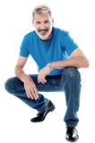 Handsome man crouching down and smiling stock images