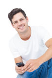Handsome man crouching using a smartphone Royalty Free Stock Photos