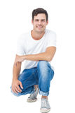 Handsome man crouching Royalty Free Stock Image