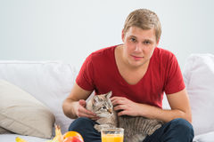 Handsome man cuddling his tabby cat Stock Photos