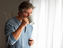 Handsome man with cup of tea near window. Stock Image