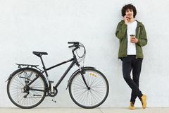 Handsome man with curly hair, dressed in green anorak, black trousers, has curly hair, speaks with girlfriend via cell phone,. Carries takeaway coffee, poses stock photos