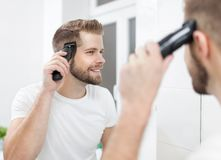 Handsome man cutting his own hair with a clipper. Handsome bearded man cutting his own hair with a clipper Royalty Free Stock Photo