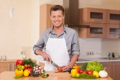 Handsome man cutting pepper on chopping board. Stock Photos