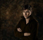 Handsome man, dark brown gothic background. Handsome man sitting over dark brown gothic background with crossed hands. Seriously looking at camera royalty free stock photo