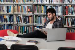 Student Studying at College. Handsome Man With Dark Hair Sitting at a Desk in the Library - Laptop and Organiser on the Table - Looking at the Screen a Concept Royalty Free Stock Photos