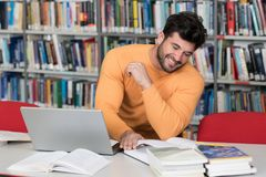 Happy Male Student With Laptop in Library. Handsome Man With Dark Hair Sitting at a Desk in the Library - Laptop and Organiser on the Table - Looking at the Royalty Free Stock Images