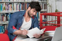 Student Studying at College. Handsome Man With Dark Hair Sitting at a Desk in the Library - Laptop and Organiser on the Table - Looking at the Screen a Concept Stock Photography