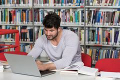 Male Student Typing on Laptop in the University Library. Handsome Man With Dark Hair Sitting at a Desk in the Library - Laptop and Organiser on the Table Royalty Free Stock Photos