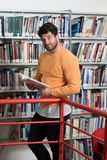 Student Learning in Library. Handsome Man With Dark Hair Standing in the Library - Student Preparing Exam and Learning Lessons in School Library Stock Photos