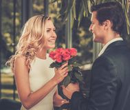 Handsome man dating his lady. Handsome men with bunch of red roses dating his lady royalty free stock photo