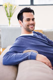 Handsome man day dreaming on the couch Stock Photography
