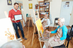 Handsome man demonstrating a painters diploma Royalty Free Stock Photo