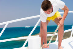 Handsome man diligently fixes rope on yacht at a sunny summer da. Y, beautiful sea on background royalty free stock image