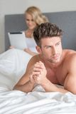 Handsome man with a displeased expression. Lying on his bed looking off to the side with a frown, because his wife is ignoring him to read on her tablet-pc Stock Photos