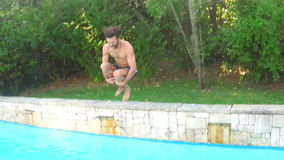 Handsome man diving into swimming pool. In slow motion stock footage
