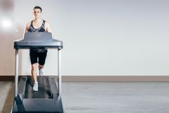 Handsome man doing cardio exercises, running on treadmills in the gym Stock Photography