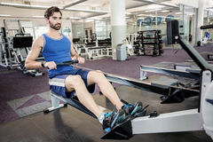 Handsome man doing exercise on drawing machine. At the gym Stock Photo