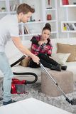 Handsome man doing housework while grilfriend relaxing. Handsome men doing housework while grilfriend is relaxing Stock Image