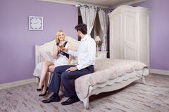 Handsome man doing a marriage proposal while offering his wife an engagement ring. Royalty Free Stock Image