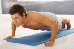 Handsome man doing push up. Handsome young man doing push up in gym on polyfoam mattress Stock Photos