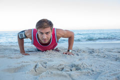 Handsome man doing push ups. At the beach Stock Photo