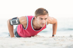 Handsome man doing push ups. At the beach Stock Photography