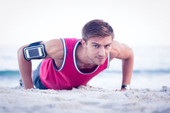 Handsome man doing push ups. At the beach Royalty Free Stock Images