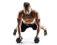Handsome man doing push ups exercise with dumbbells. Royalty Free Stock Photography