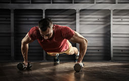 Handsome man doing push ups exercise with one hand in fitness gym royalty free stock image