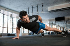Handsome man doing push ups exercise. Portrait of a handsome man doing push ups exercise with one hand in fitness gym Royalty Free Stock Photos
