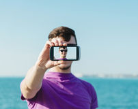 Handsome man doing a self-portrait with smartphone Royalty Free Stock Images