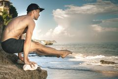 Handsome man doing yoga at cliff with blue sea background Stock Photo