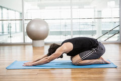 Handsome man doing yoga on mat Stock Image