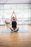 Handsome man doing yoga on mat Stock Photography