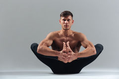 Handsome man doing yoga pose. On a white background Stock Image