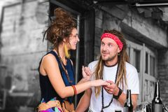Handsome man with dreadlocks taking hand of his lovely appealing girlfriend
