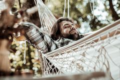 Handsome man dreaming about something in a hammock