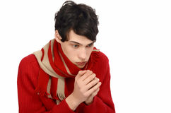 Handsome man dressed for a cold winter being cold, with hands freezing. Royalty Free Stock Photography