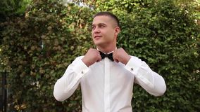 Handsome man dressed outside. White shirt and black bow tie. Classical look for man.  stock video footage