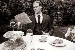Man dressed in suit drinks esperesso at a cafe table. Handsome man dressed in vintage classical suit drinking coffee at cafe table while reading newspaper Stock Image